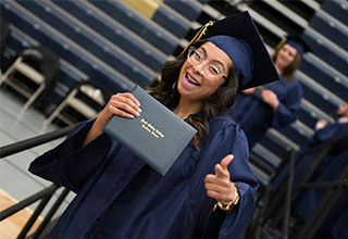 A female student holds up diploma at graduation ceremony.