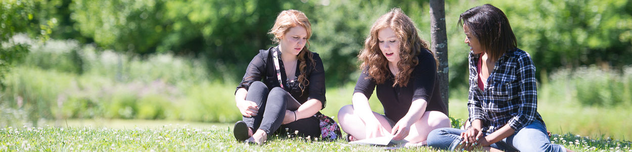 Three female students sitting in the grass studying on campus.
