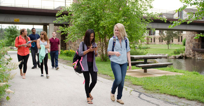 Students walking on campus near the creek.