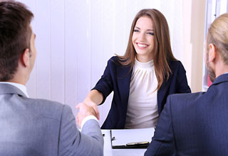Woman shaking hands with man at job interview.