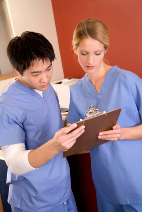 Two nurses consulting a chart.