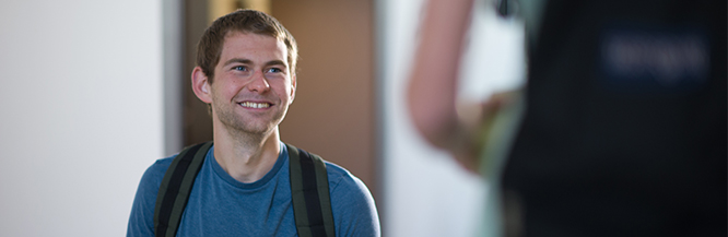 Male student smiling while walking up stairs on main campus.