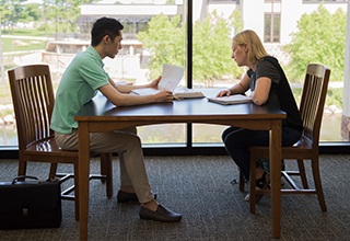 Two students sitting inside the Library looking over papers and written notes