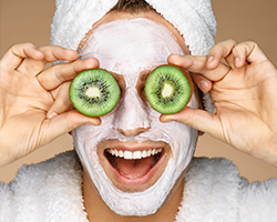 Woman with cucumbers on her eyes and a face mask on