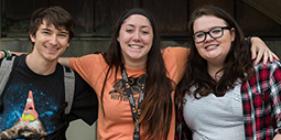 Three students sitting outside of RVC's main campus Student Center Atrium at an event