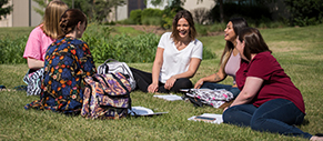 Female students sitting on the grass outside of the JCSM