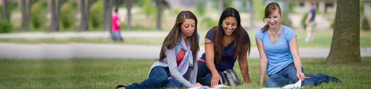 Three female students in the grass studying on our campus.