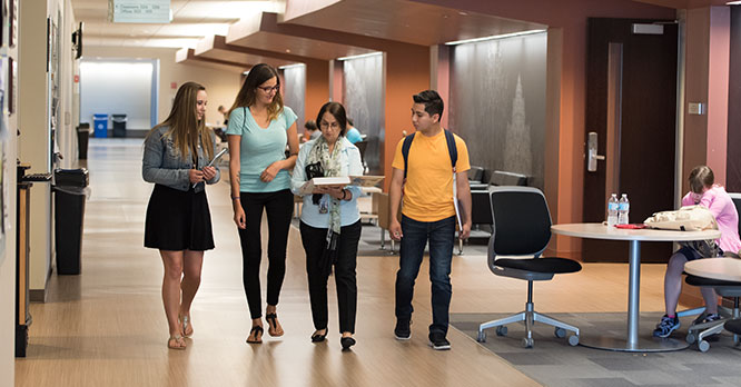 Students walking in the Jacobs Center with a professor